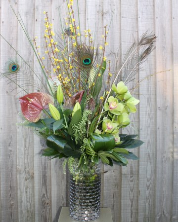 Vase Display Of Cymbidium Orchid, Lily, Anthurium, Forsythia and Peacock Feathers With Foliage
