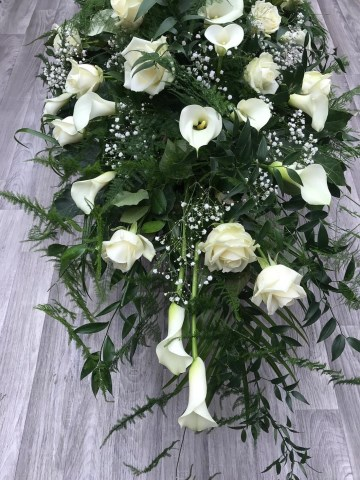 white Rose and Calla Lilly casket spray with soft trailing fern