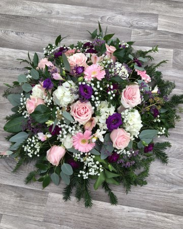 pink and purple posy display - fuberal tribute posy design - pink roses germini freesia - purple lisianthus - limonium - ivory hydrangea gypsophilia