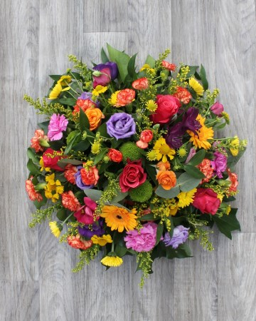 vibrant posy display - funeral tribute posy design - germini - lisianthus - rose -xanths - yellow pink purple and orange flowers