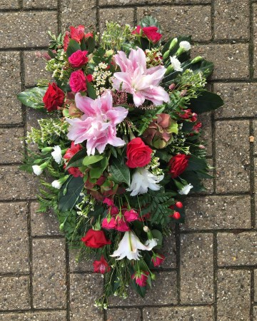 pink cerise and red single ended spray funeral tribute design - pink double lily - cerise rose and spray rose - red rose and alstromeria - ivory carnation and waxflower