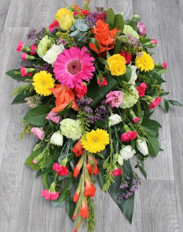 vibrant single ended spray  funeral tribute design - cerise gerbera and spray cars - yellow germini , solidaster and roses - orange gladioli - green carnation - purple limonium