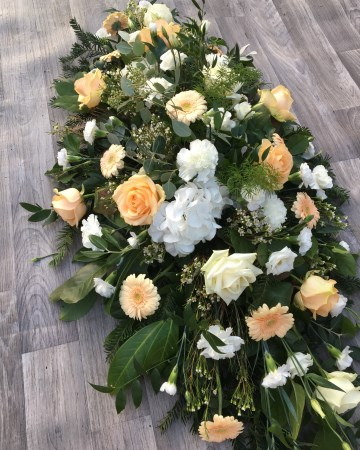 ivory and peach casket spray - funeral tribute design - ivory roses, carnations, hydrangea and waxflowers with peach germini and mixed foliages
