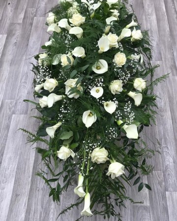 ivory rose and calla lilly casket spray with mixed foliages and trailing fern - white funeral tribute design