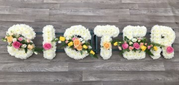 sister funeral tribute display - foliage edge - based in white chrysanthemums - pink peach and yellow sprays - peach yellow and pink roses - lisianthus - mixed foliages