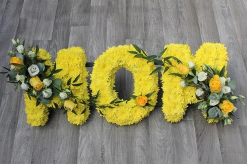 Mom funeral tribute design - based in yellow chrysanthemums - yellow and white sprays - yellow roses - white lisianthus - white spray rose - mixed foliages